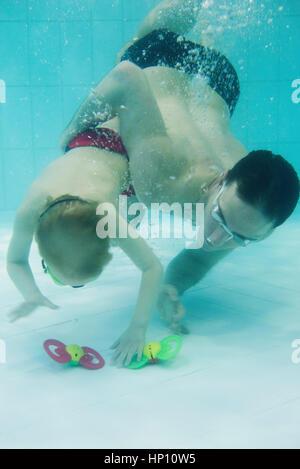 Padre ayudando boy nadar hasta el fondo de la piscina para recuperar toy