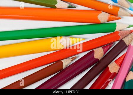 Cerca de varios lápices de colores sobre fondo blanco.