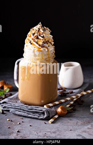 Caramel iced latte con crema batida y jarabe sobre fondo oscuro
