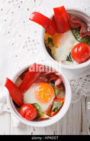 Huevo frito con espinacas, pimientos, tomates y queso en una taza de cerca en la tabla. vista vertical desde arriba