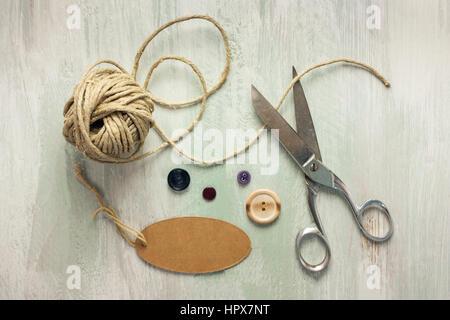 Una foto del vintage tijeras con un rollo de cuerda, una etiqueta con el espacio, y los botones de copia, tomada desde arriba sobre tablones de madera ligera textura de fondo