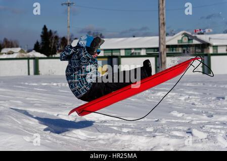 Un joven (4 años) saltar en el aire en un trineo en invierno Quebec