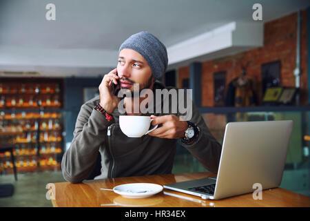 Joven apuesto hipster hombre con barba sentado en la cafetería hablando de teléfonos móviles, sosteniendo una taza de café. Ordenador portátil sobre la mesa de madera.