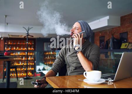 Joven apuesto hipster hombre con barba sentado en la cafetería con una taza de café, vaping y libera una nube de vapor. Hablando de teléfonos móviles y tener un pequeño descanso. Foto de stock