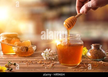 Mano con penetrador miel recogida en un tarro de miel. Los tarros de miel, panal de abeja y polen sobre mesa de madera con flores en una rústica cocina y s