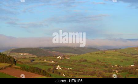 Montañas Cambrian, Gales, Reino Unido. 8 de marzo de 2017. El clima del Reino Unido - Después de un día de temperatura primaveral, una banda de nubes iluminadas por el sol vespertino se cierne sobre las montañas Cambrian cerca de Aberystwyth, Gales, Reino Unido. Crédito: John Gilbey/Alamy Live News