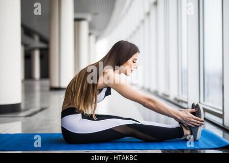 Un gran progreso. Joven bella mujer en ropa deportiva haciendo estiramientos mientras está sentado en el suelo, delante de la ventana en el gimnasio