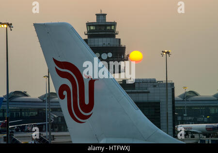 Puesta de sol detrás de la Torre de Control del Tráfico Aéreo en Hong Kong el aeropuerto Chek Lap Kok