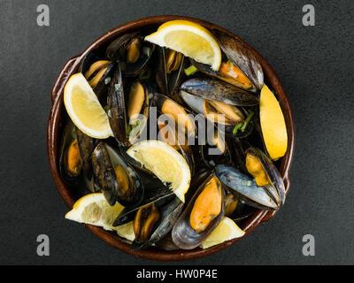 Cuerda de mejillones cultivados en una salsa de ajo y chalota con rodajas de limón