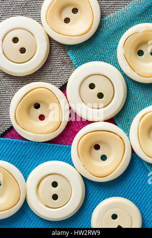 Concepto con botones monofónicos beige sobre trozos de tela de color plano, macro, vista superior, plano laical.