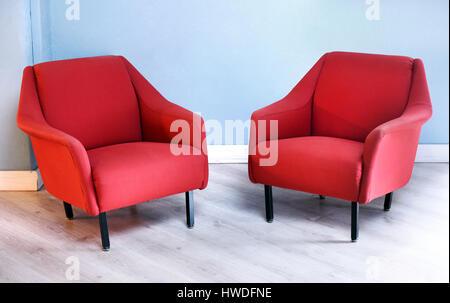 Muebles todavía la vida del par de sillones Vintage de felpa roja con patas negras en la sala con piso de madera y paredes de color azul claro