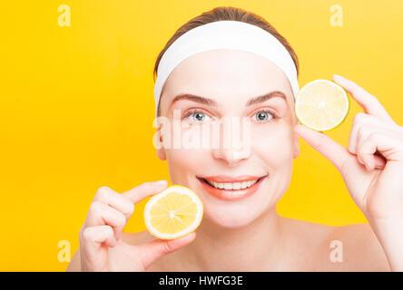 Concepto de belleza y cuidado de la piel con gozosa mujer mostrando rebanadas de limón y lima sobre fondo amarillo