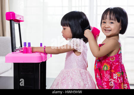 Chino Asia Hermanitas jugando con maquillaje juguetes en casa.