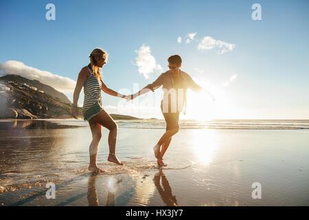 Disparo de longitud completa de la joven pareja tomados de la mano caminando por la playa y divertirse. Mujer joven y disfrutar de unas vacaciones a la orilla del mar. Foto de stock