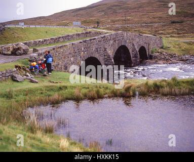 Los ciclistas por el puente de piedra, la Isla de Skye, Inner Hebrides, Highland, Scotland, Reino Unido Foto de stock