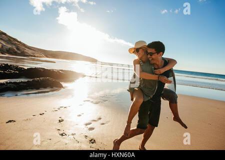 Romántica pareja joven disfrutando de sus vacaciones de verano. Apuesto joven dando piggyback paseo a la novia en la playa.