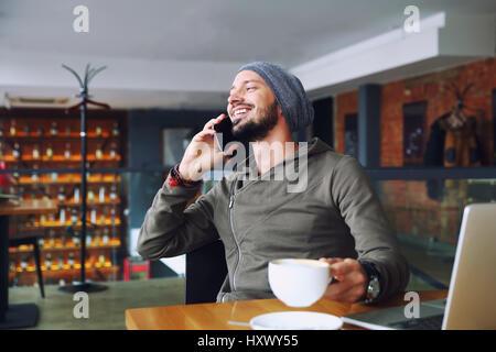 Joven apuesto hipster hombre con barba sentado en la cafetería hablando de teléfonos móviles, sosteniendo una taza de café y sonriente. Ordenador portátil sobre la mesa de madera.