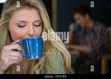 Close-up de joven bebiendo café en la cafetería
