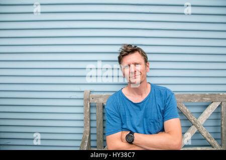 California, Estados Unidos, Pacific Grove, hombre sentado en el viejo banco de madera Foto de stock