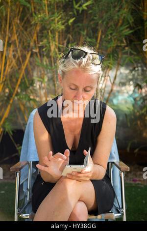 California, Estados Unidos, Santa Bárbara, mujer madura, sentada en la silla al aire libre y el uso de teléfono celular