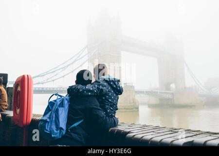 Reino Unido, Inglaterra, Londres, mitad hombre adulto celebración boy (8-9) mientras mira el Tower Bridge en la niebla Foto de stock