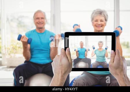 Mano sujetando recortadas contra la tableta digital retrato de pareja senior sonriente sosteniendo pesas