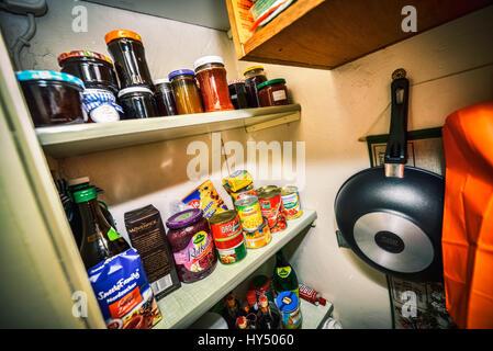 Despensa con los alimentos enlatados, las latas y tarros de embotellado, mit und Einmachglaesern Konservendosen Speisekammer