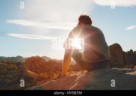 California, Estados Unidos, el Parque Nacional Joshua Tree, el hombre sentado sobre una roca y observar el atardecer