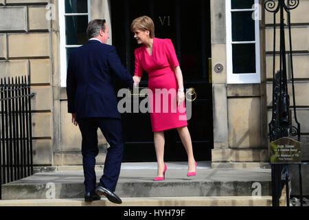 El Primer Ministro de Escocia, Nicola Sturgeon saluda al Primer Ministro David Cameron como él llega para entrevistarse en el Bute House en Edimburgo Foto de stock