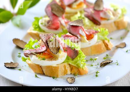 Canapés con roast beef , otoño Negro Trufa, queso brie francés sobre una rebanada de huevo en baguette con una hoja de ensalada