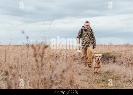 Caminante y pasear perros pequeños amarillos en los prados en un día nublado