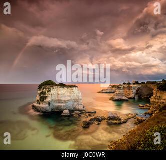 Arco iris después de la tormenta y los relámpagos en los acantilados conocidos como Faraglioni di Sant'Andrea, provincia de Lecce, Puglia, Italia