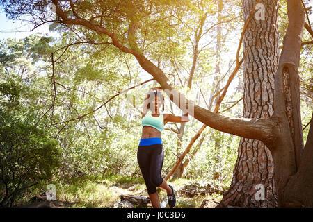 Retrato de joven mujer vistiendo ropa deportiva, en entorno rural