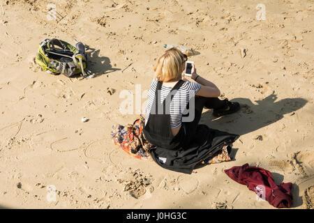 Una solitaria mujer sentada sola en la playa al lado del río Támesis, cerca de South Bank de Londres.