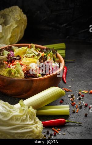 Recipiente de madera con una mezcla de ensalada de congelación, Lollo Rosso, radicchio, romano y el iceberg con zanahorias sobre fondo negro