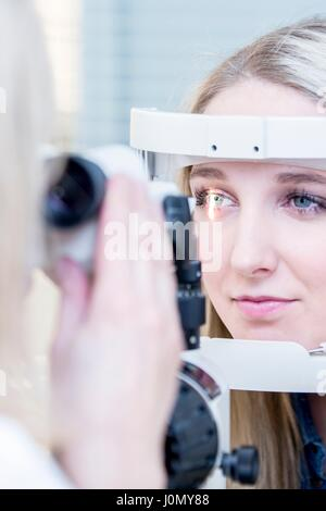 Paciente de sexo femenino, con un examen de los ojos en el optometrista de la tienda, cerca.