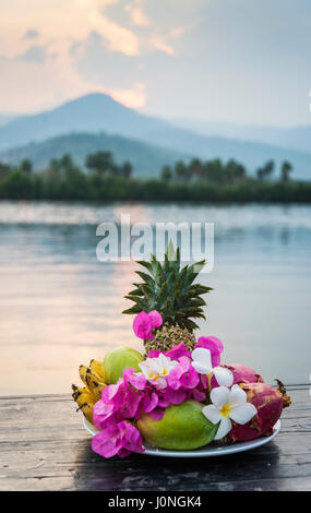 Frutas exóticas flores tropicales y placa de selección al atardecer en Kampot Camboya