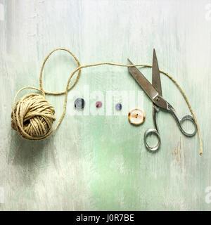 Un cuadrado foto de vintage tijeras con un rollo de hilo y botones, disparó desde arriba sobre tablones de madera ligera textura de fondo, con copyspace