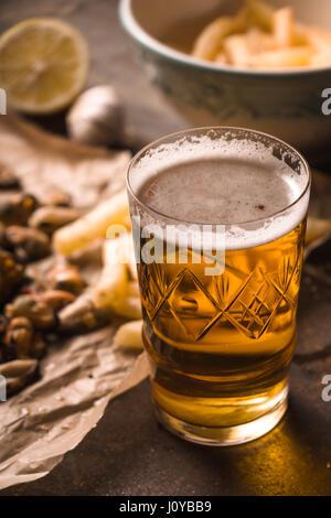 Vaso de cerveza con snack borrosa en el fondo de metal