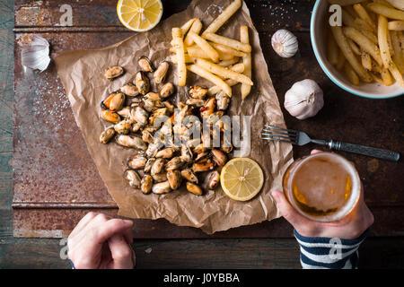 Bebiendo cerveza con mejillones y patatas fritas vista superior