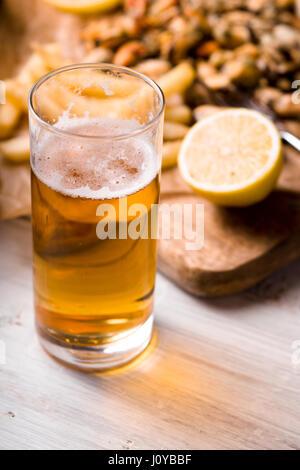 Vaso de cerveza con snack borrosa sobre la mesa de madera blanca