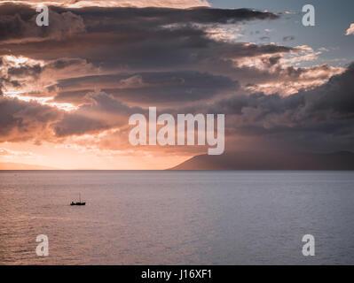 Pequeño barco de vela en el mar al atardecer con grandes nubes arriba