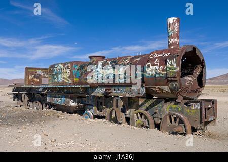 Antigua locomotora oxidada salpicada con Graffiti solitaria permanente en el Cementerio de los trenes, el mayor Foto de stock