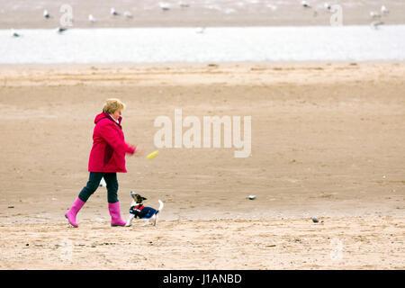 Una mujer lanza una bola para su perro Jack Russell en la playa en el popular balneario de Rhyl en Denbighshire, al norte de Gales, en rojo brillante capa