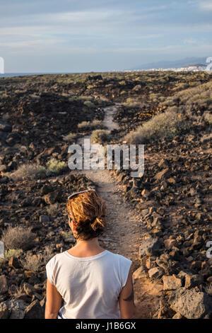 Mujer caucásica de pie en camino a través de las rocas Foto de stock