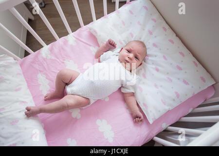 Niña de dos semanas durmiendo en su cuna en hojas rosadas con patrón nuboso.