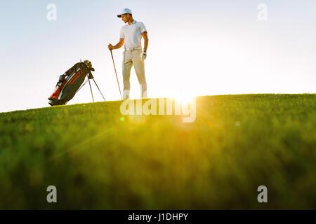 La longitud total del jugador de golf mirando mientras está de pie en el campo de bolsa durante el día soleado. Tiros de ángulo bajo macho golfista en el campo de golf.