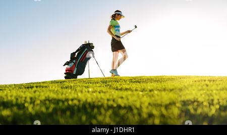 Bajo el ángulo de filmación profesional Golfista Femenina en campo de golf. La longitud total del jugador de golf el campo de golf el palo.