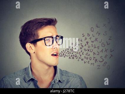 El perfil lateral hombre hablando con las letras del alfabeto que sale de su boca. La comunicación, la información, el concepto de inteligencia