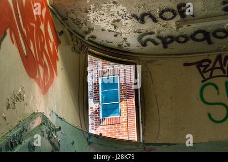Detalle del interior del piso superior escalera con ventana abierta en la fábrica Unigate abandonados, Gran Torrington, Foto de stock